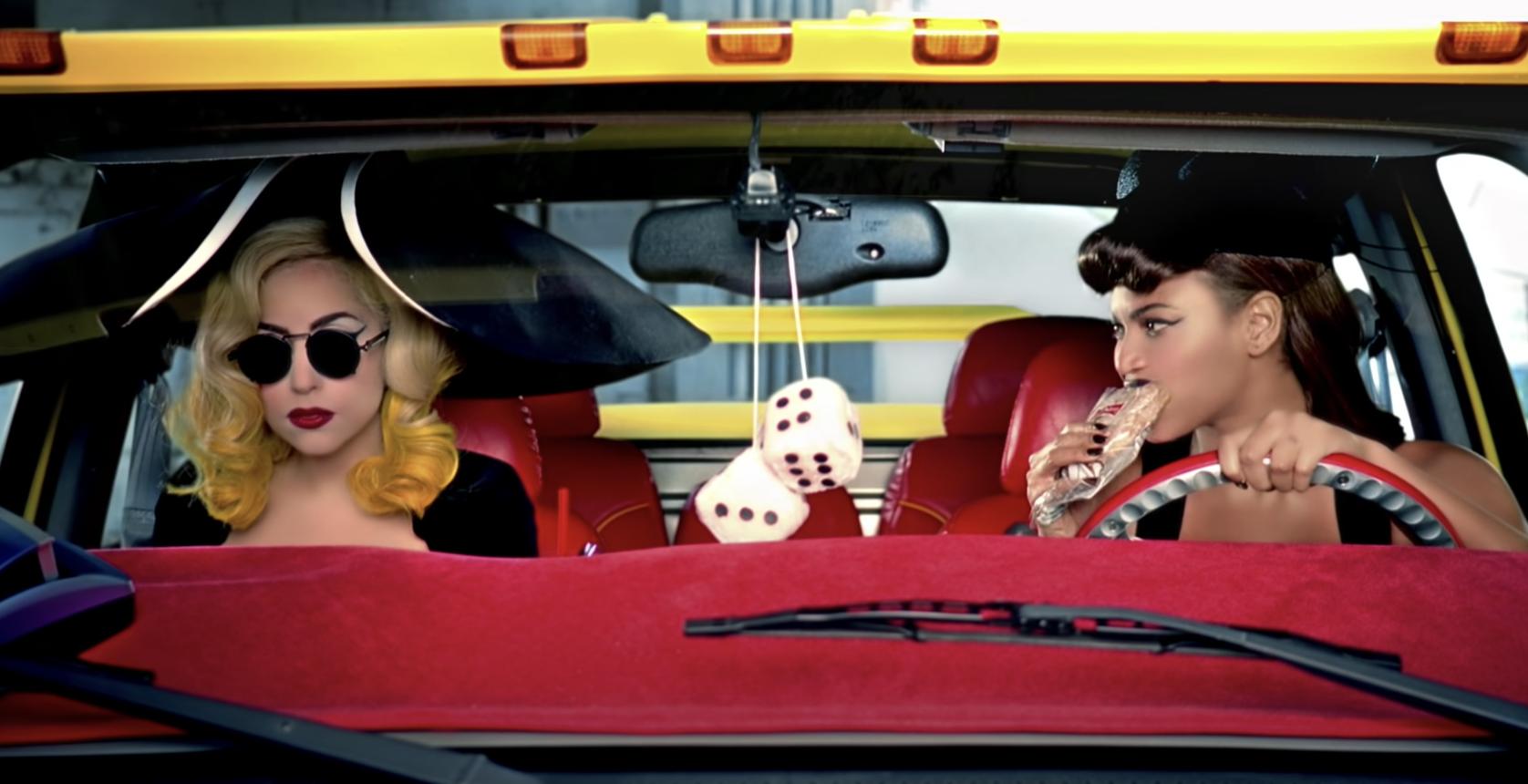 Beyonce eating a sandwich as she picks up Lady Gaga