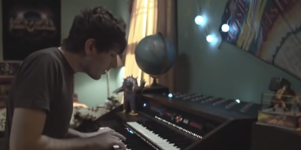 Owl City playing piano in a bedroom