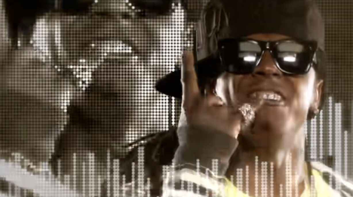 Lil Wayne in sunglasses and a hat pointing up