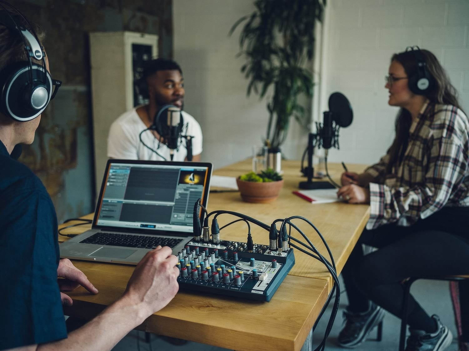 Three people sitting in a room with microphones. One of them is using the mixer.