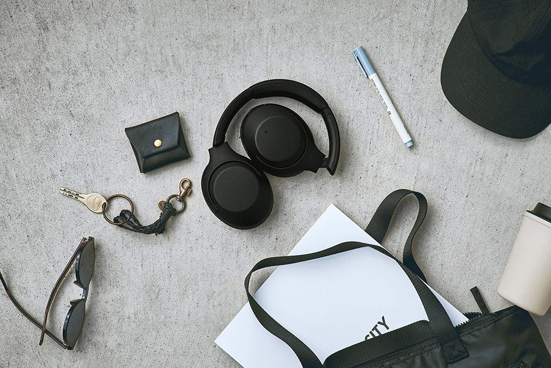 A pair of headphones besides various items such as keys, sunglasses, etc.