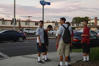 A group of kids stand on a sidewalk corner and look around