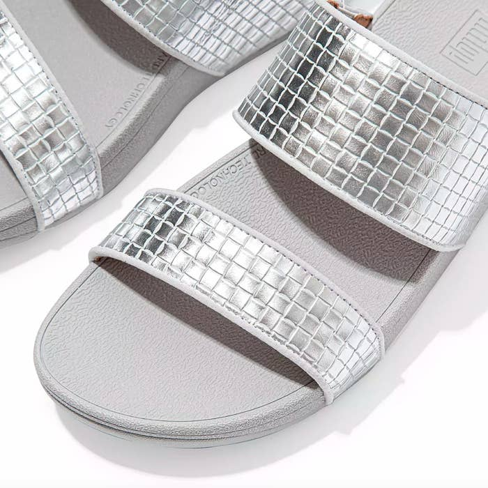 The pair of metallic leather slides in silver