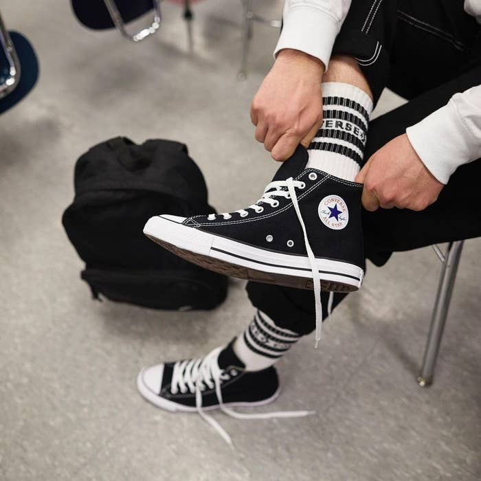 model putting on black all-star high-tops with logo on ankle, white laces, and white toe cap