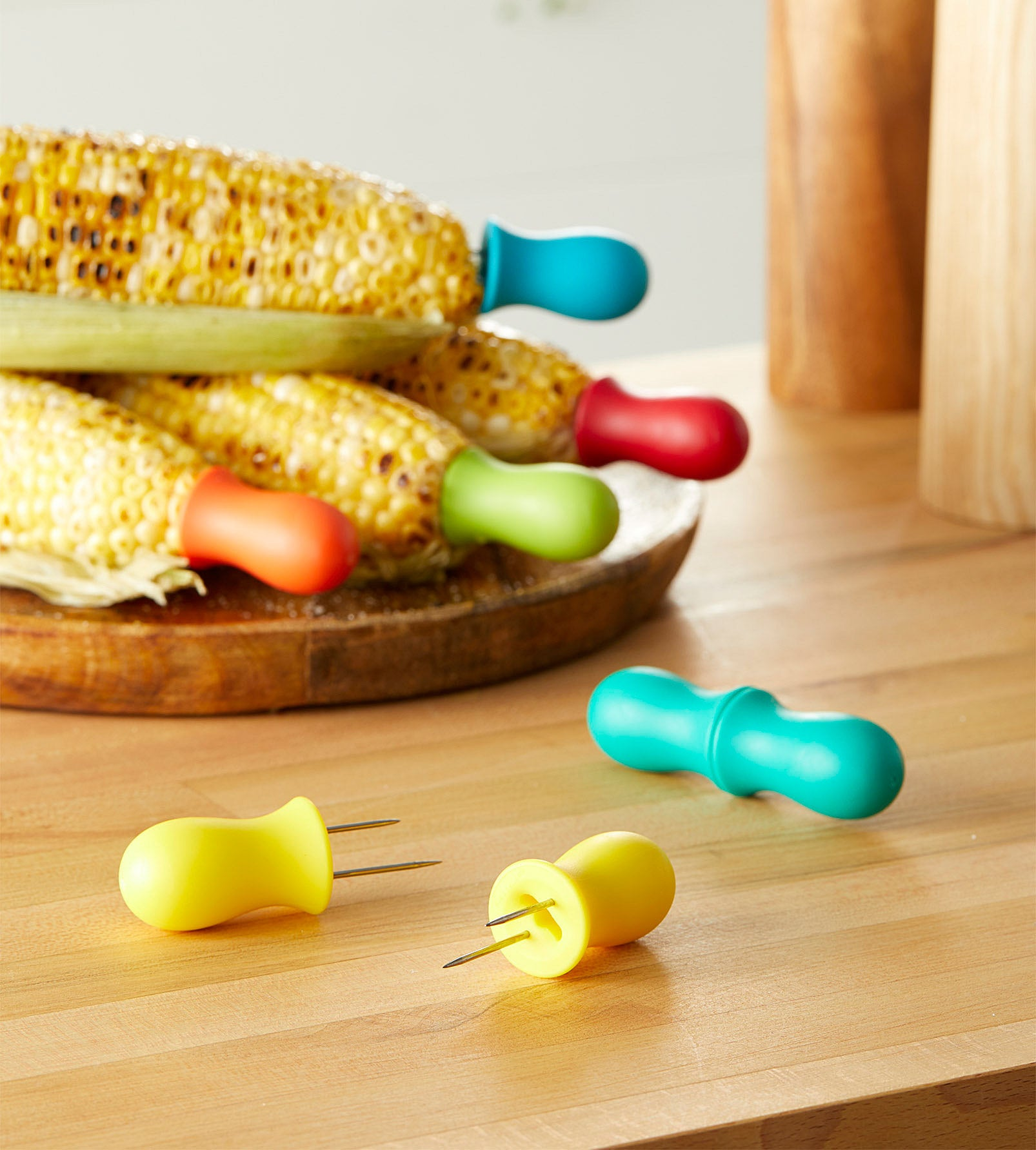 A set of colourful corn cob holders attached to grilled cobs