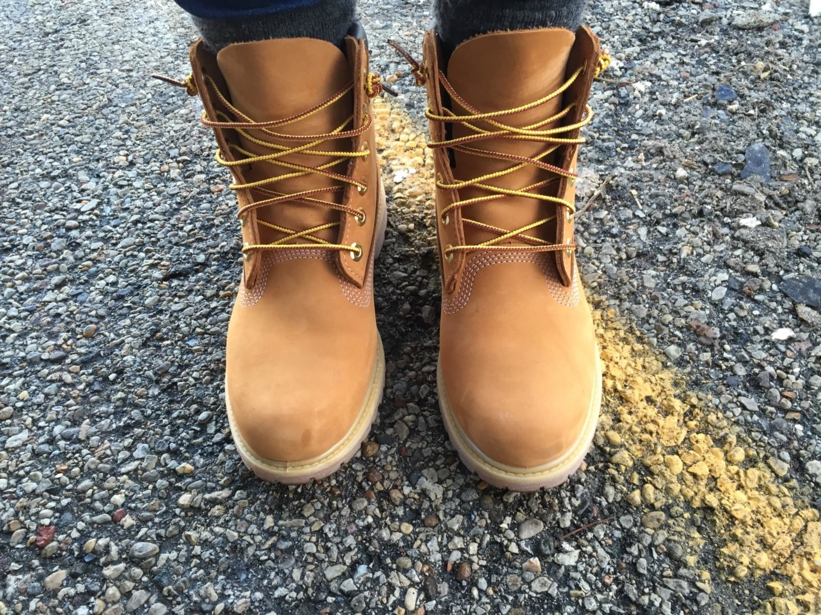 reviewer in the taupe lace-up high-top leather boots with lug soles and woven laces