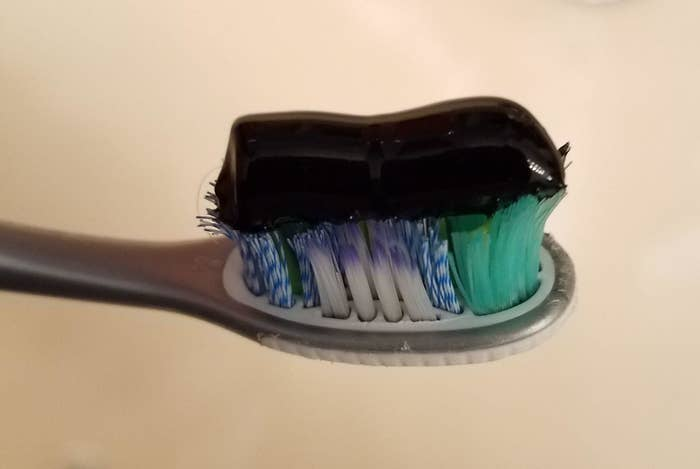 reviewer image of the black tom's of maine activated charcoal toothpaste on a toothbrush