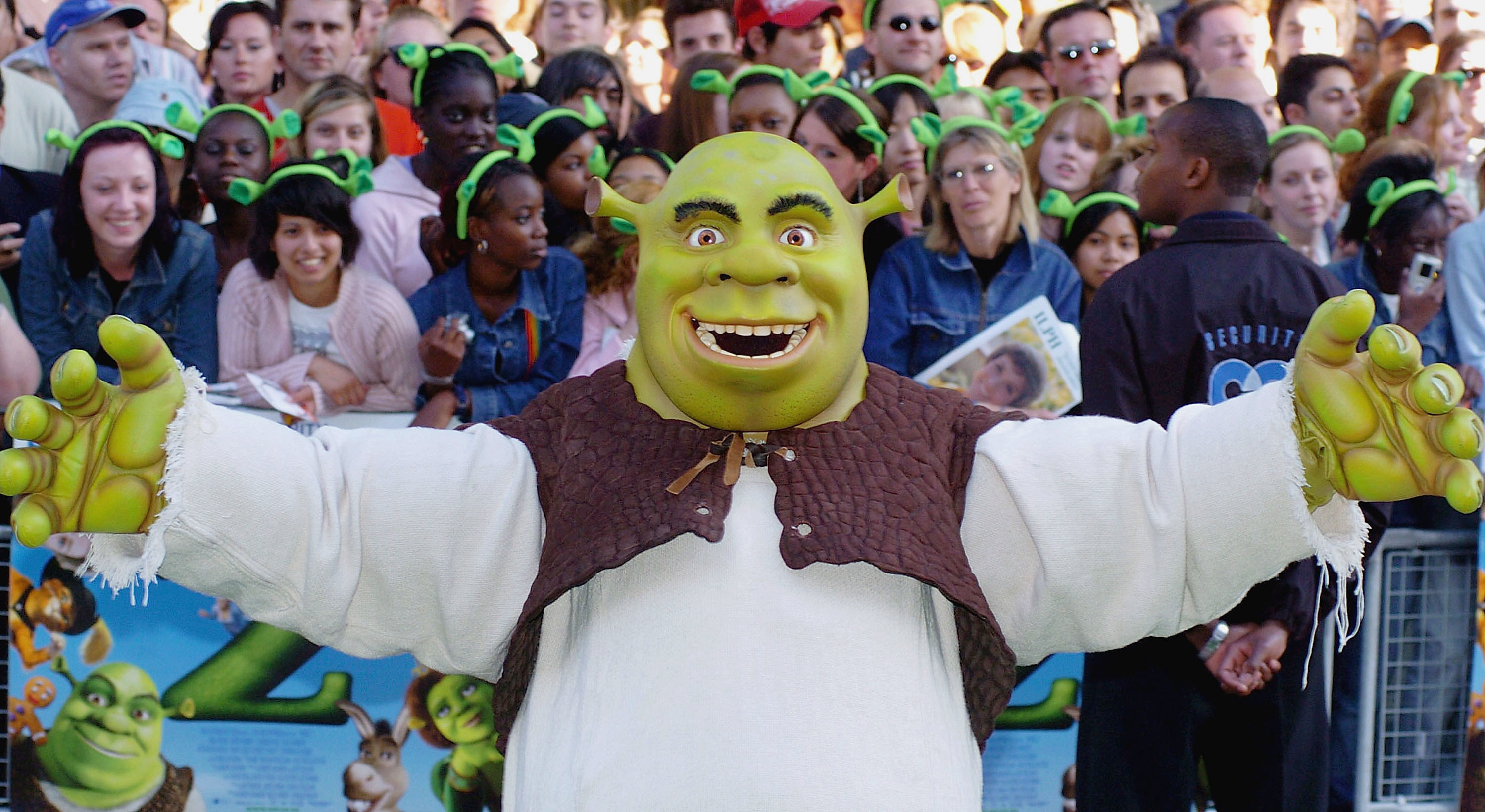 Someone in a Shrek costume holds their arms wide in front of a crowd of people wearing green headbands of ogre ears