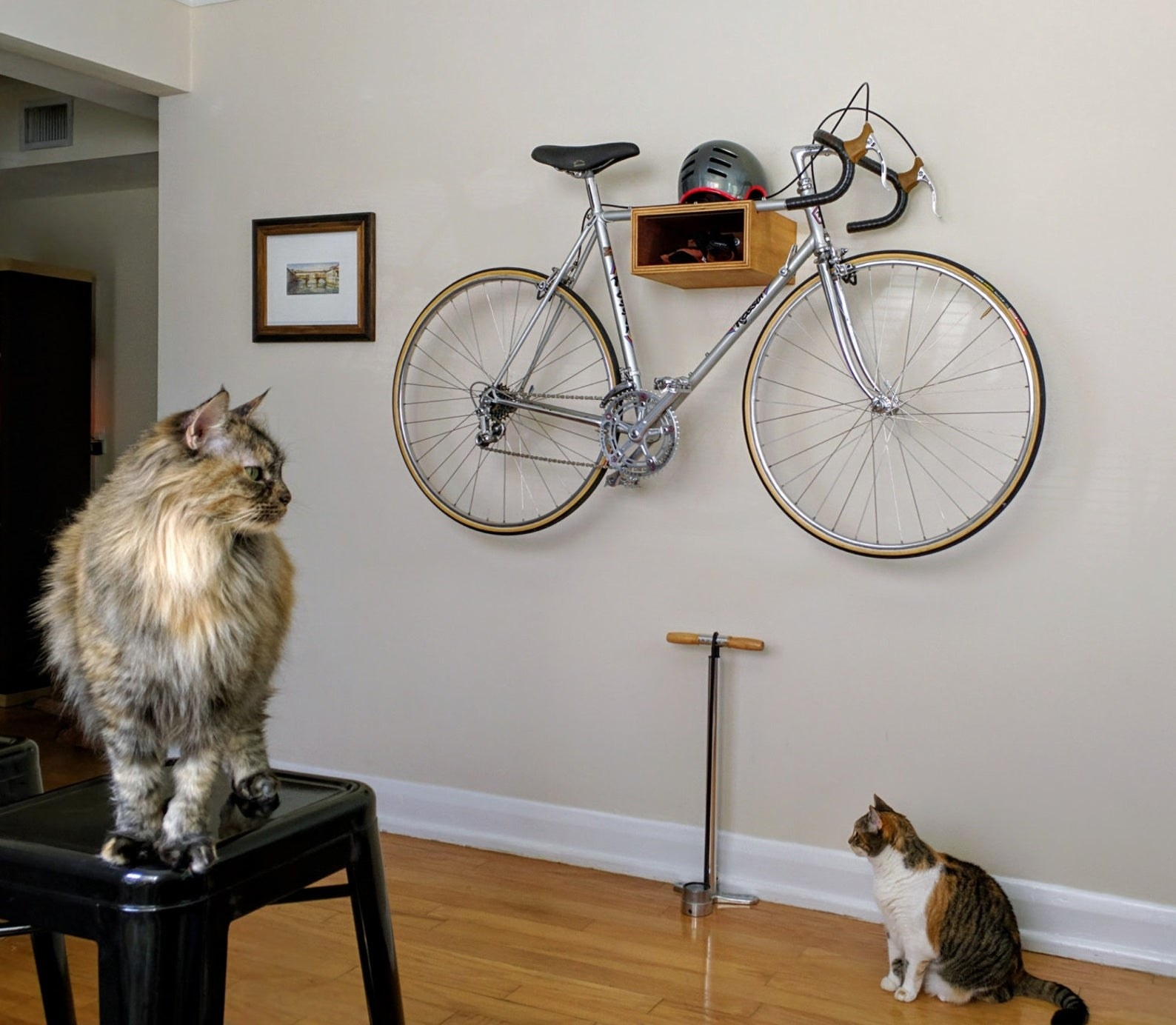 A wooden bike rack mounted to the wall with bike hanging from it