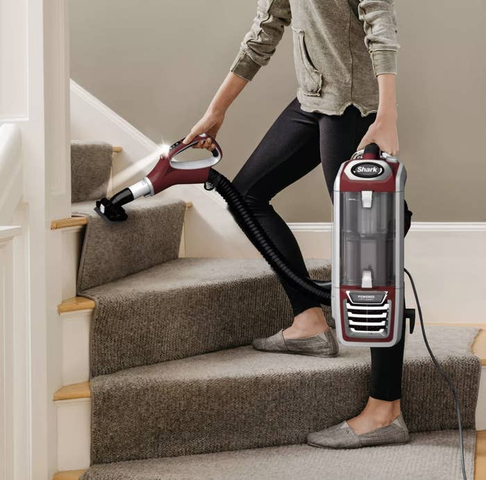 person using the small attachment from vacuum to easily clean stairs