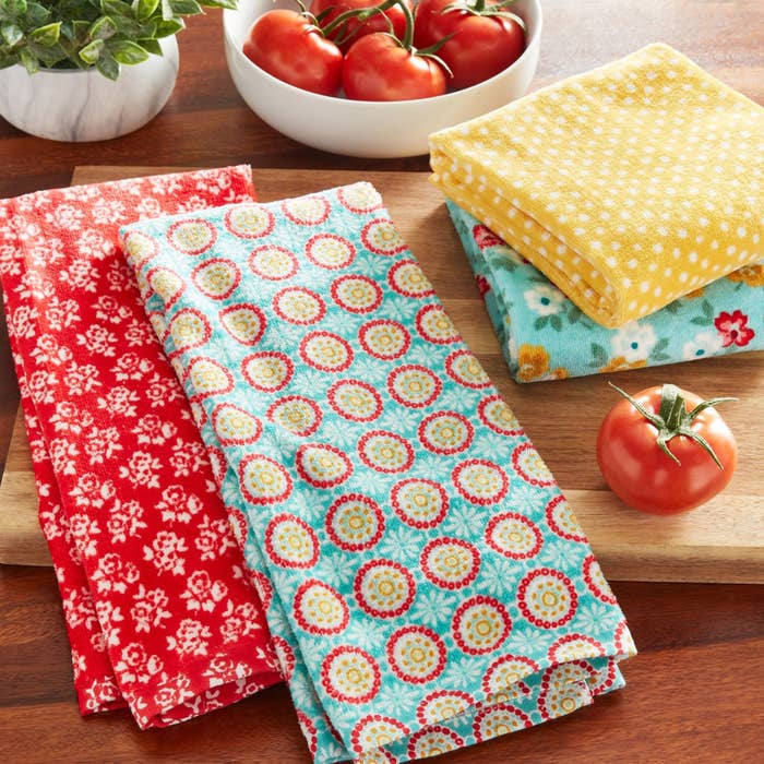 the kitchen towel set with one red and white towel, one yellow with polka dots, and one blue with a red and yellow flower pattern