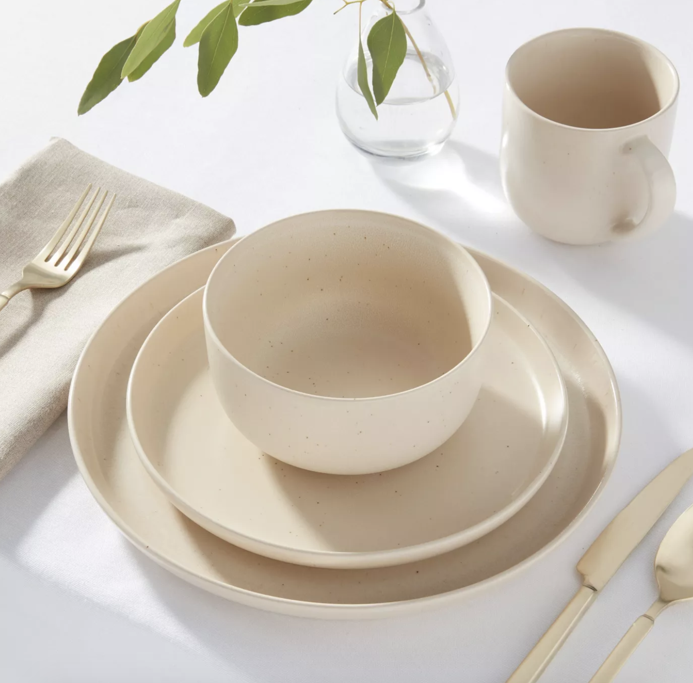 cream colored stoneware set with two plates, bowls, and mugs