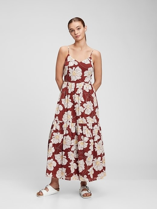 a person wearing a floral, maxi dress with spaghetti straps