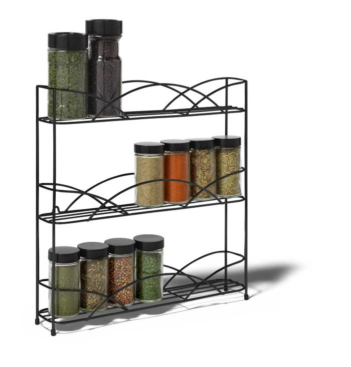the wire spice rack with unlabeled spice bottles on it