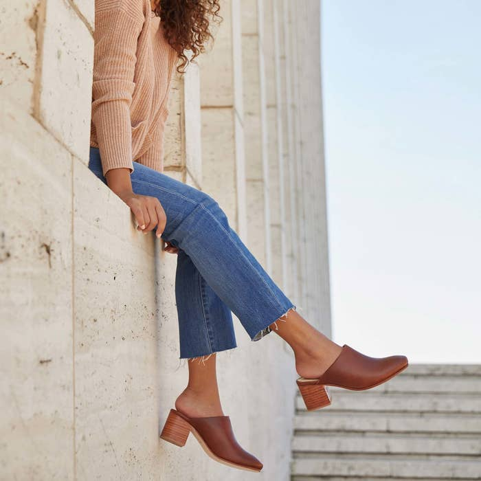 model wearing leather slip on mules with small heel
