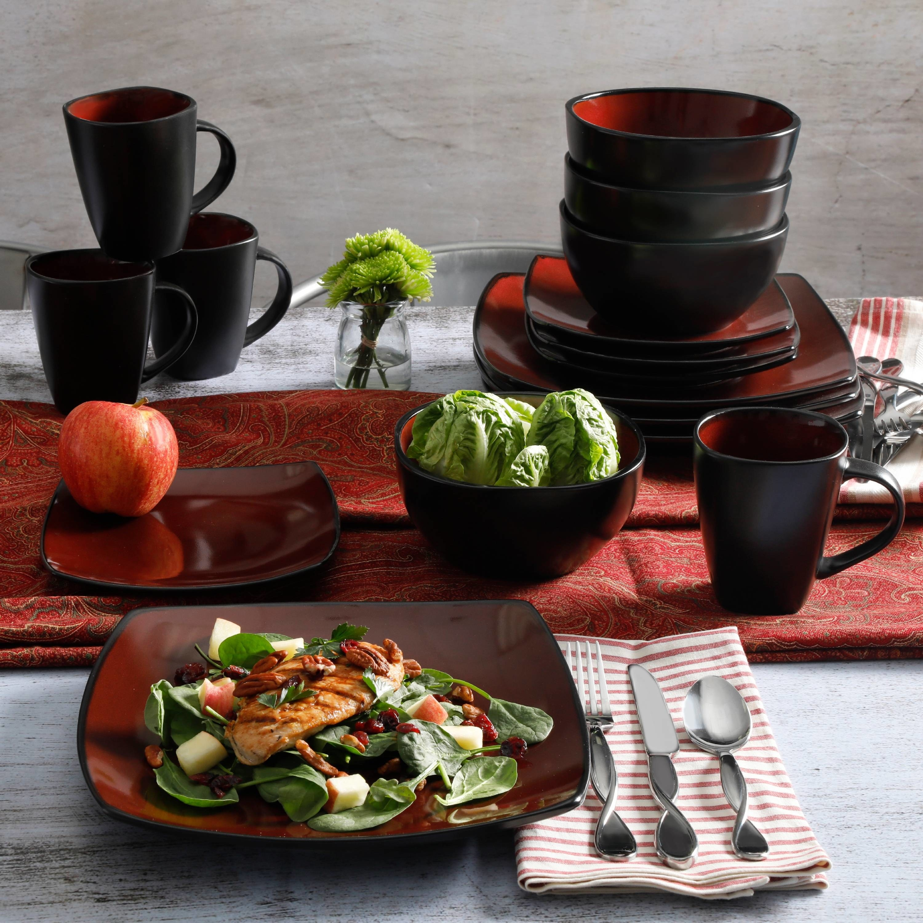 the red and black dinnerware set with salad and chicken on the plate