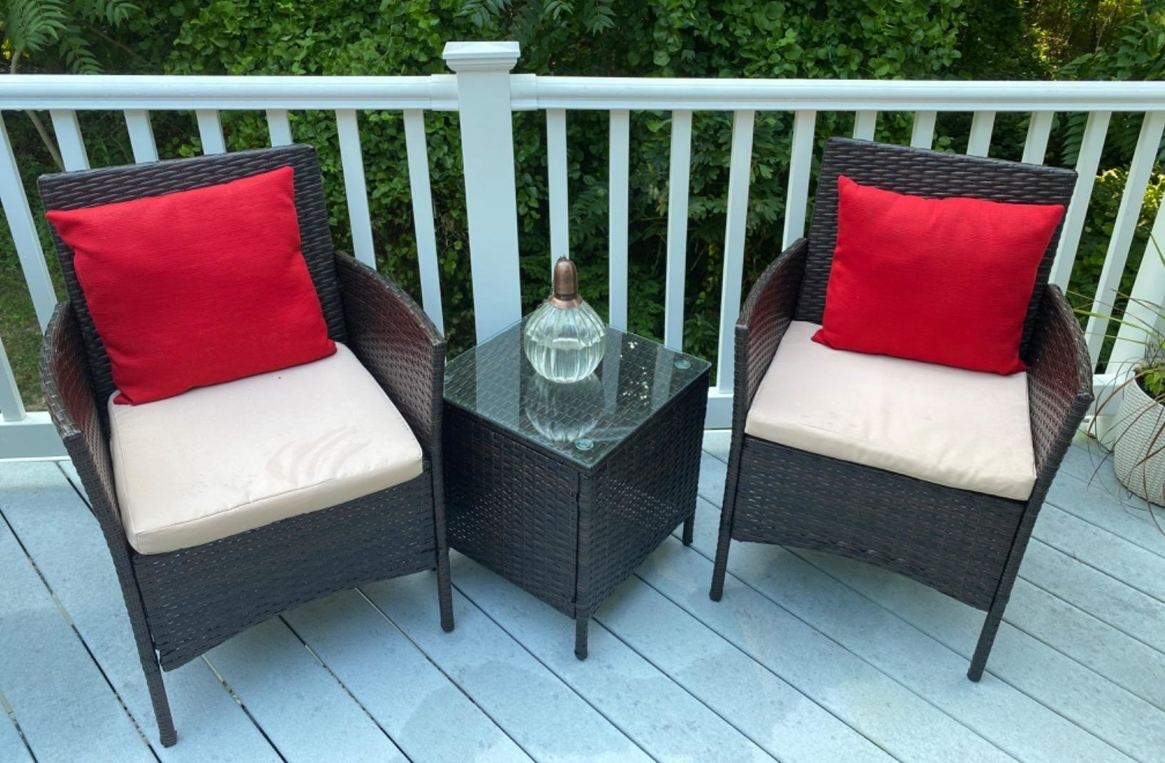 a reviewer photo of two rattan arm chairs with a matching side table with a glass top