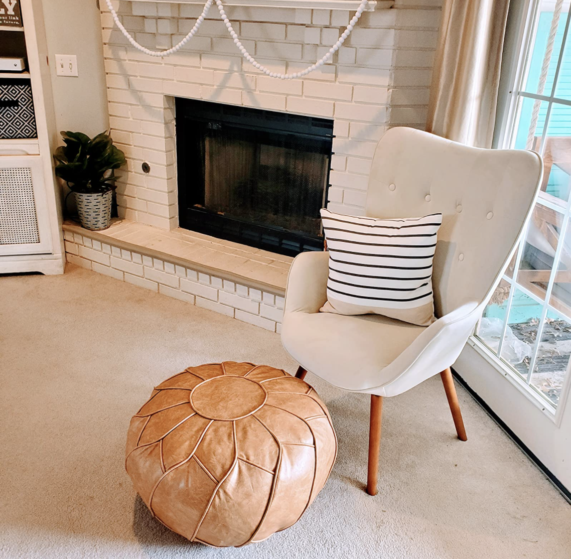 Reviewer's light brown leather pouf is styled in a room.