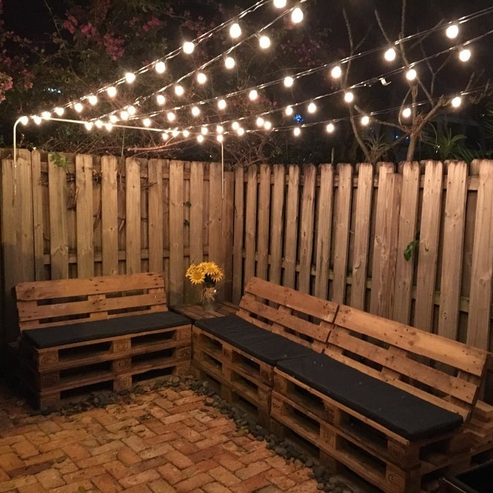 a reviewer photo of a backyard with strings of lights handing above a set of benches