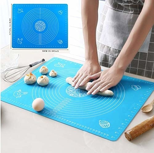 Dough being rolled out by hand on a blue silicone baking mat