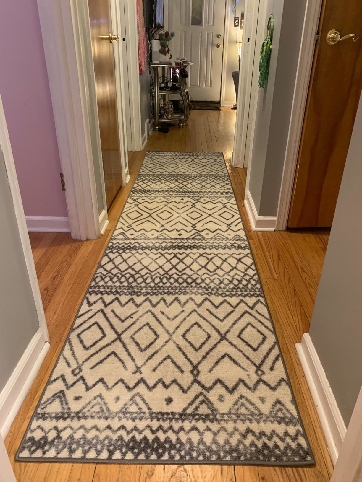 a reviewer photo of the carpet runner in a hallway in a neutral beige with a dark colored pattern