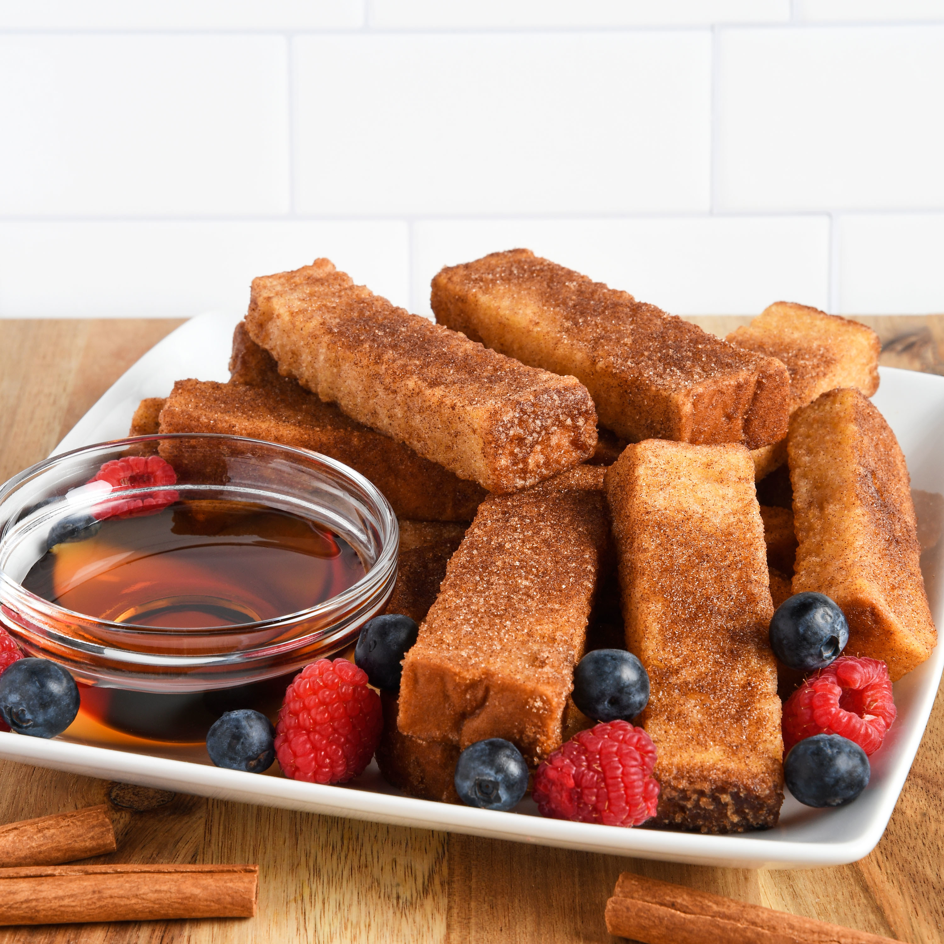 Plate of french toast sticks with raspberries and blueberries