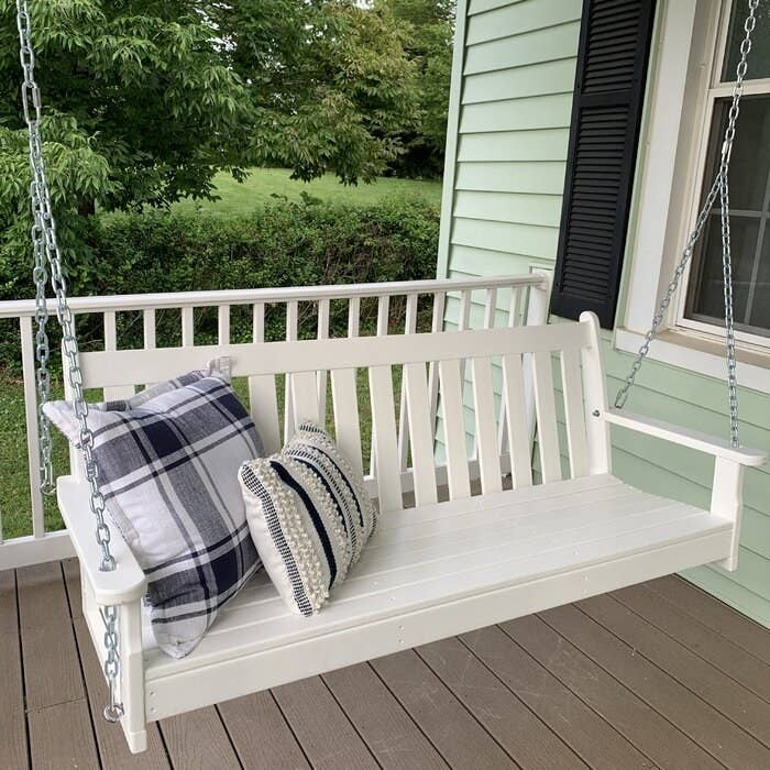 a reviewer photo of their porch swing in white hanging on their front patio with decorative pillows on it