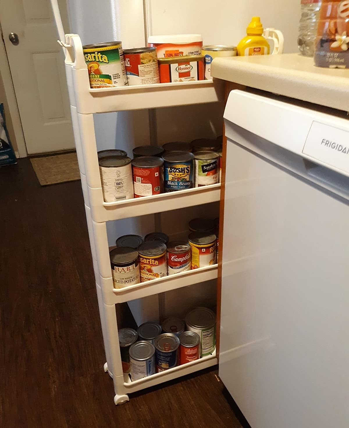 Reviewer image of the rack, which holds cans and other items on shelves that are slightly covered on the edges so that the cans cannot fall off easily