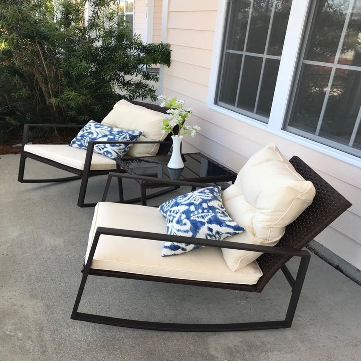 a reviewer photo of the two rocking chairs with cream cushions with a matching side table between