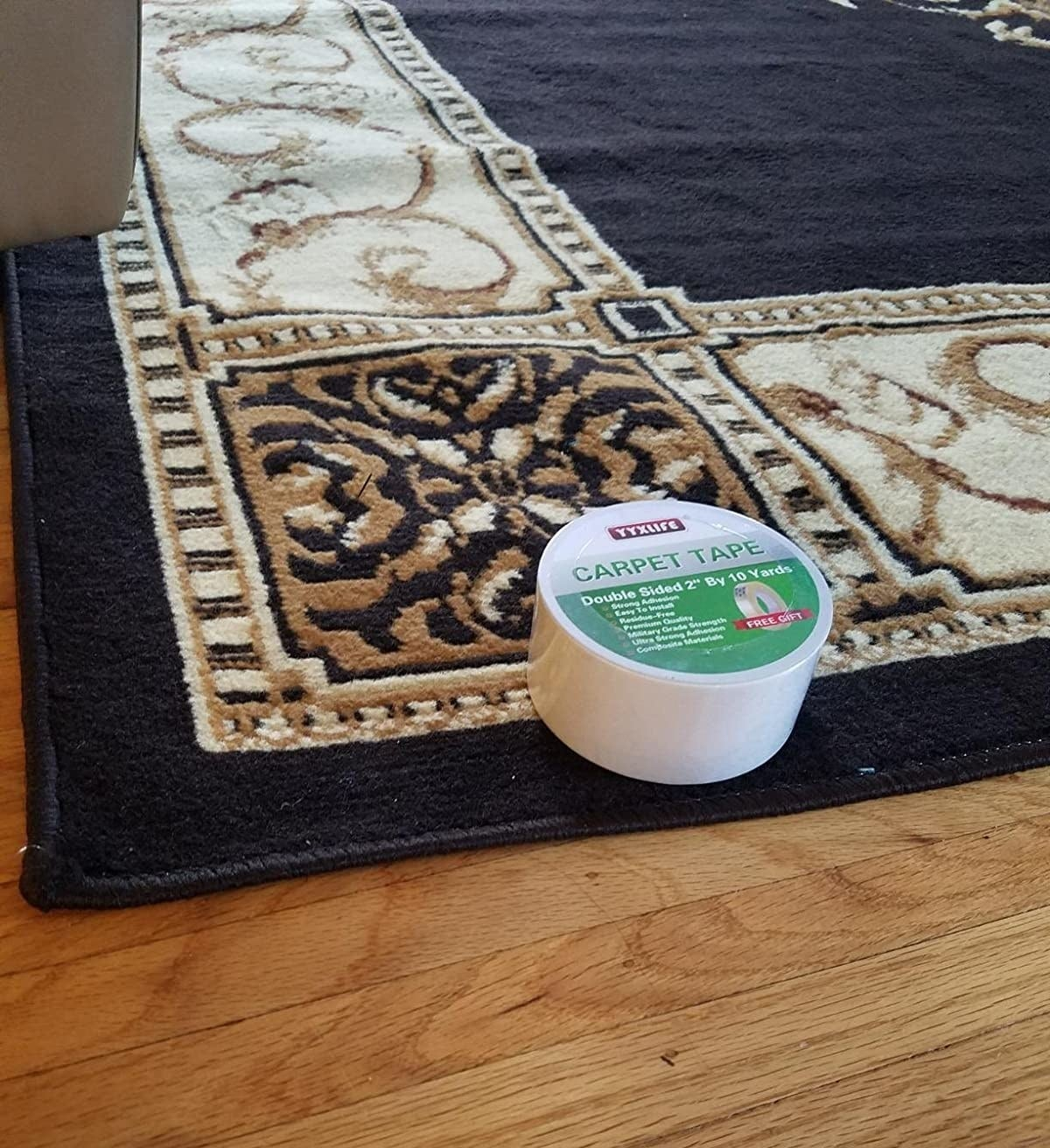 reviewer's rug on wood floor with a roll of the tape