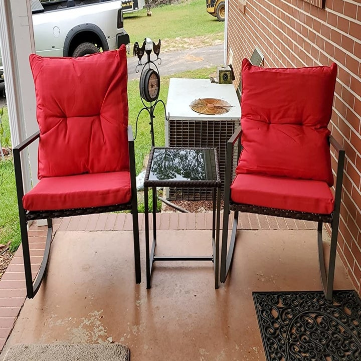 a reviewer photo of a pair of rocking chairs with red cushions with the matching side table between