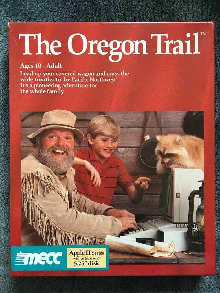 """A box for one of the early versions of """"The Oregon Trail,"""" complete with a mountain man using an Apple II computer with a raccoon on top of it"""