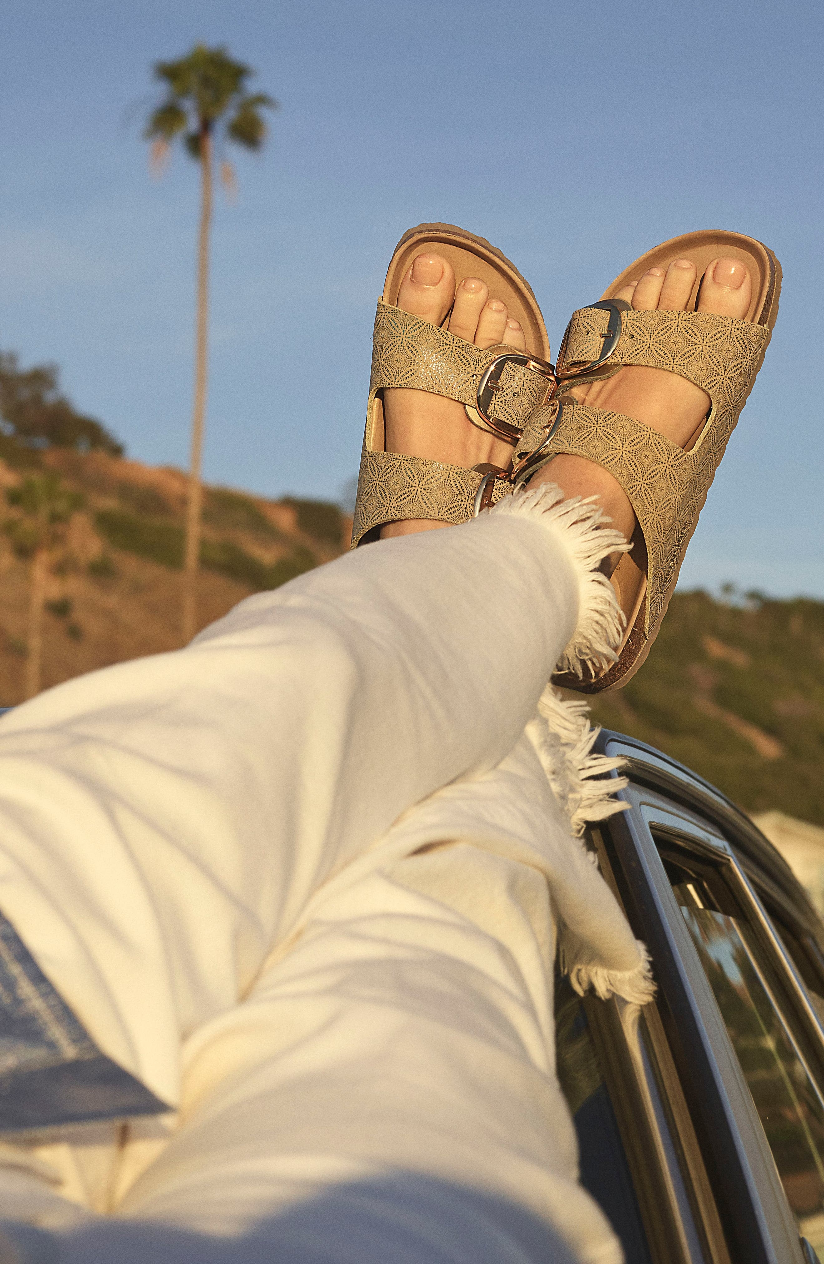 model's feet wearing two-strap flat sandal with a big shiny buckle on each strap