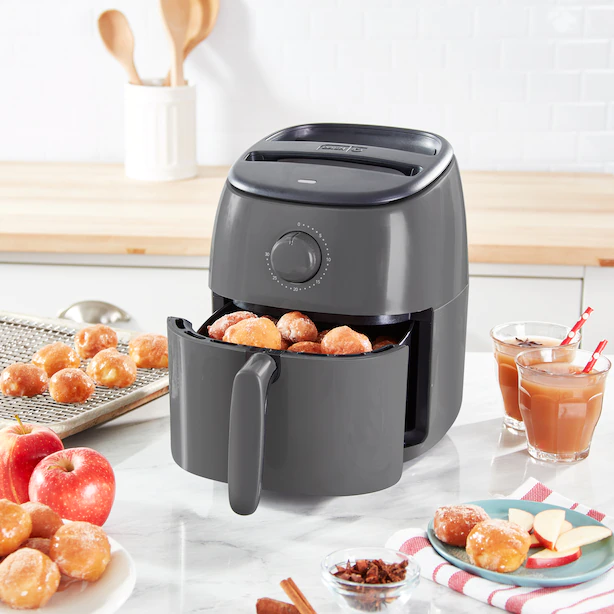 An air fryer open with little donut holes on the basket and a plate of apple slices beside it