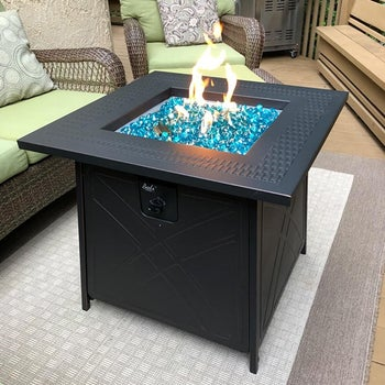 reviewer's fire pit lit up on their patio