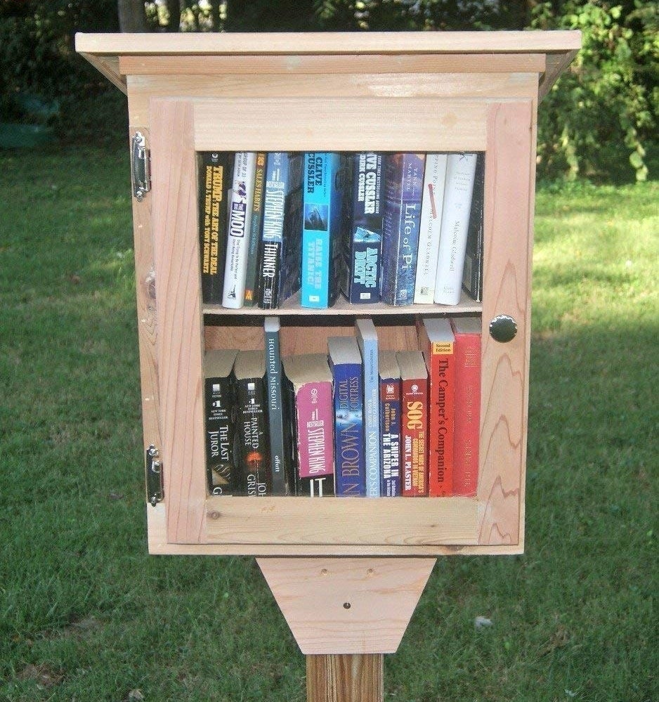 a cedar box on a stake featuring a clear glass door with books inside
