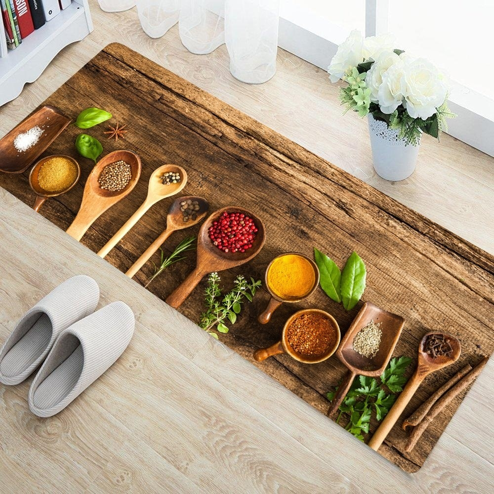 A runner with a gorgeous photo of spoonfuls of spices digitally printed on it, kept on the floor with slippers in front of it and a plant above it.