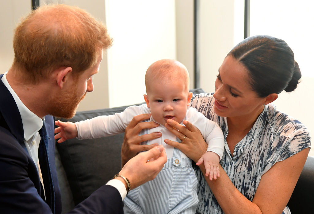 Prince Harry (L) and Meghan Markle tend to their baby son Archie Mountbatten-Windsor