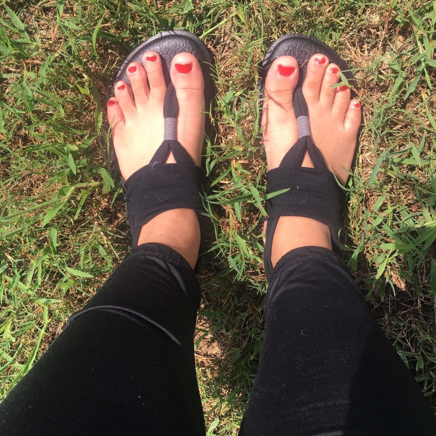 reviewer wearing the flat shoes thong sandals with black soles and black straps