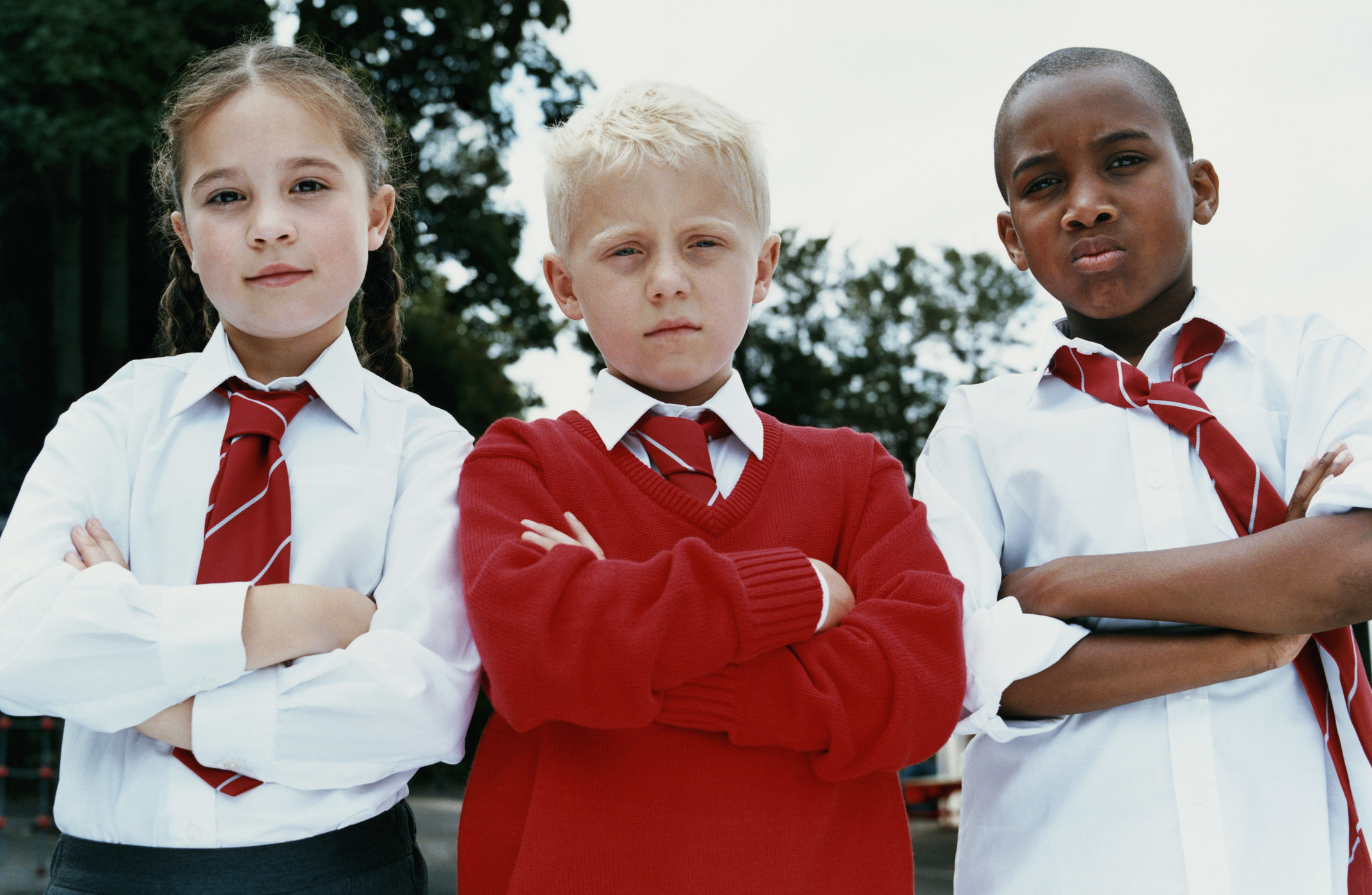 Portrait of three primary school children standing with their arms folded, scowling at the camera and wearing uniforms with ties