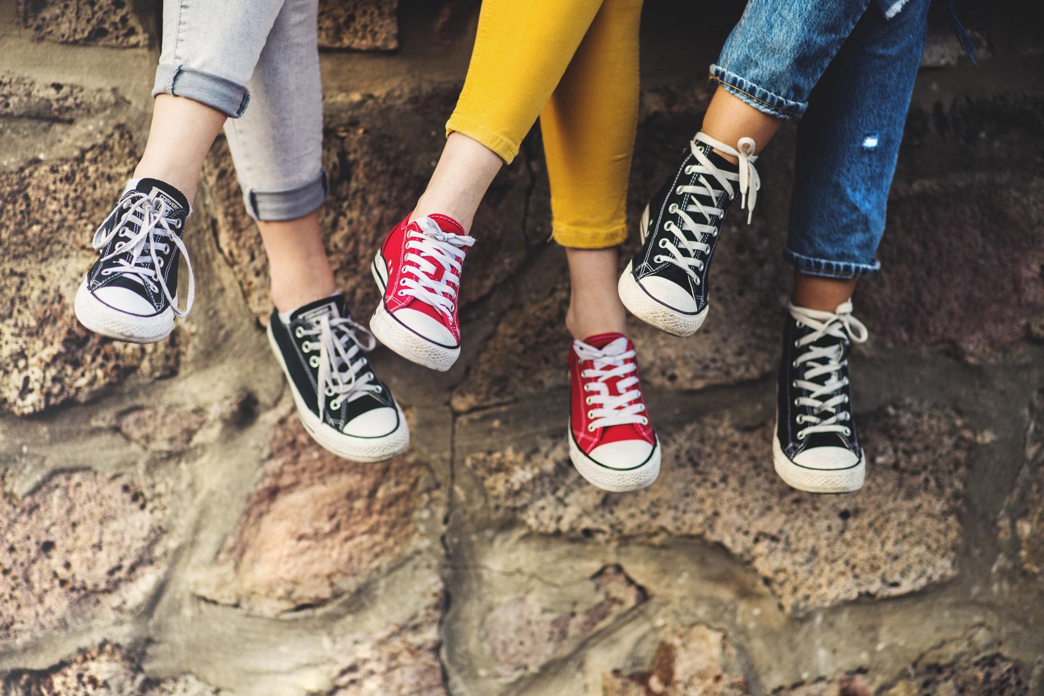 Legs of three female teenager friends sitting cross-legged on a wall, wearing sneakers