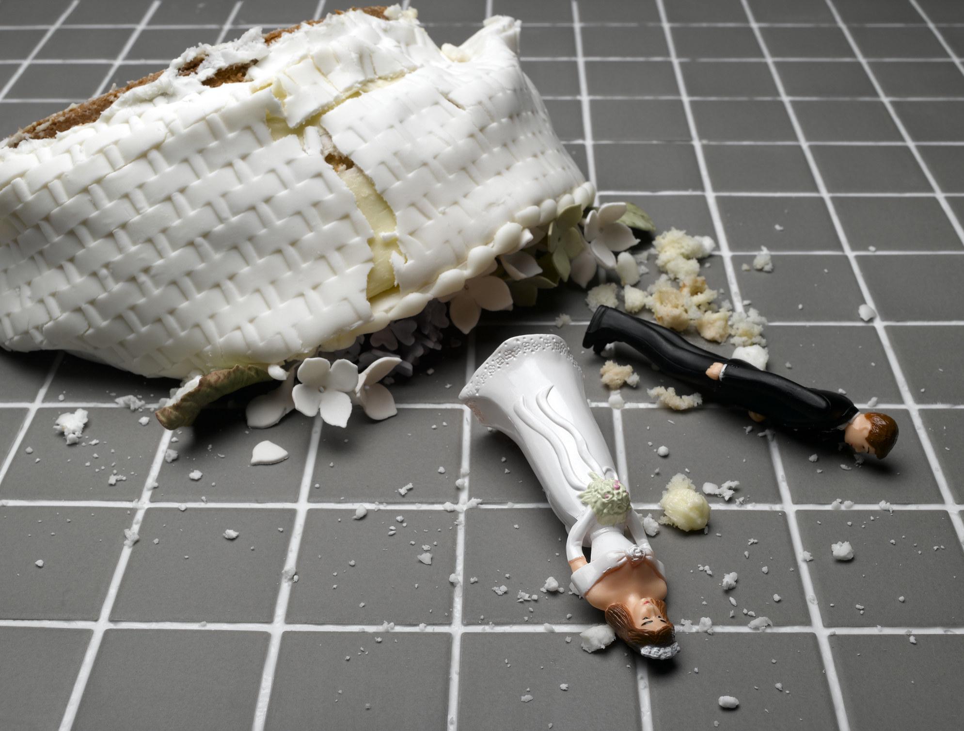 一个婚礼蛋糕被毁坏在地板上,新娘和新郎的动作人物在地板上