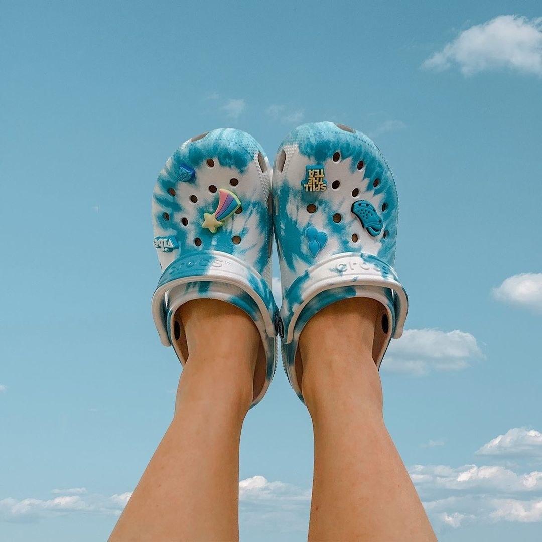 model wearing blue and white swirl tie-dye foam mules with ventilation holes