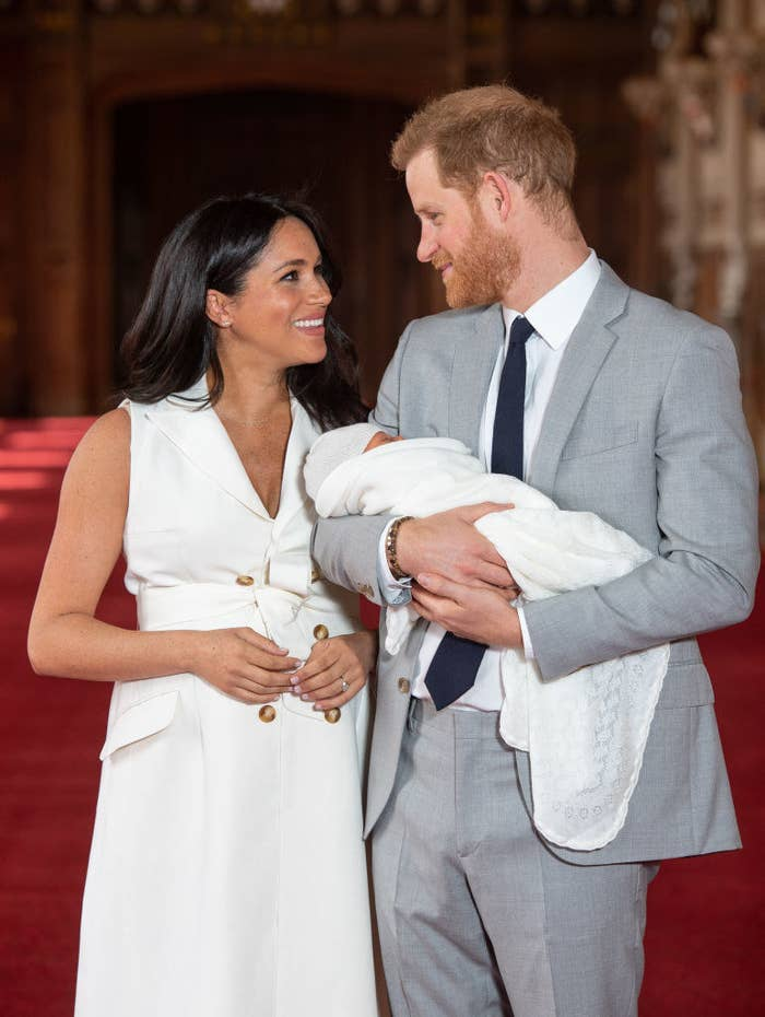 Prince Harry (R) and Meghan Markle pose with their newborn son Archie Harrison Mountbatten-Windsor