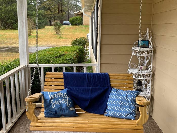 a reviewer photo of their porch swing and the decorative pillows on the swing the pillows are blue and one reads home sweet home and the other is patterned