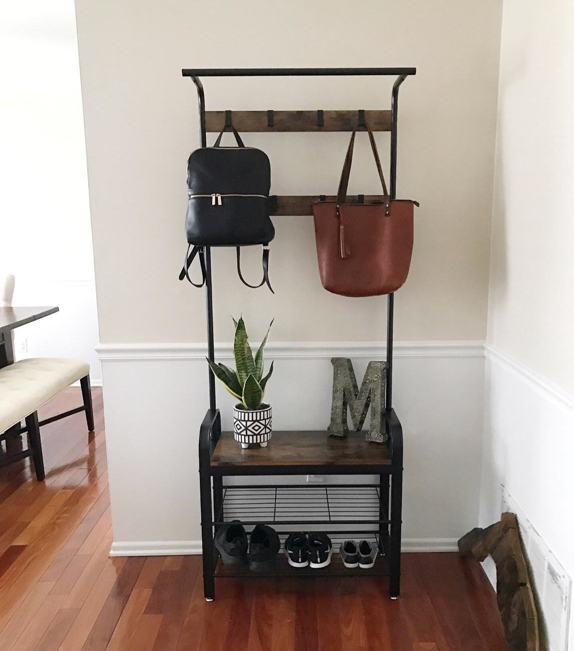a reviewer photo of their entry way organizer with shoes on the bottom a couple of purses hanging from the hooks at the top and a plant and decorative letter M sitting on the shelf