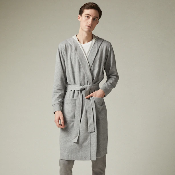 A person wearing a robe over sweatpants