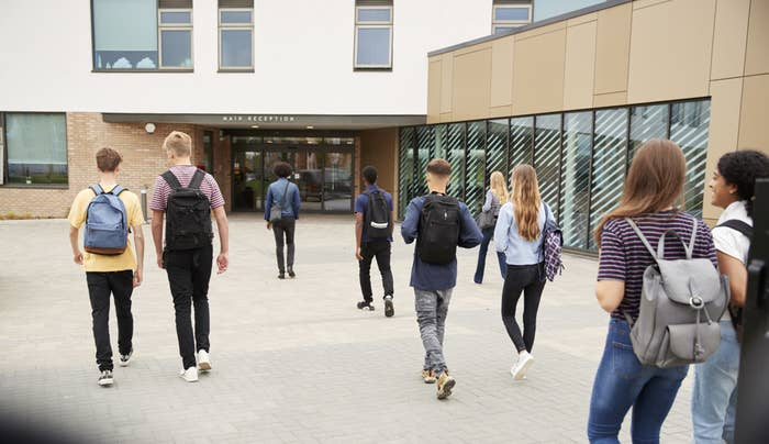 Rear view of high school students walking into a building together