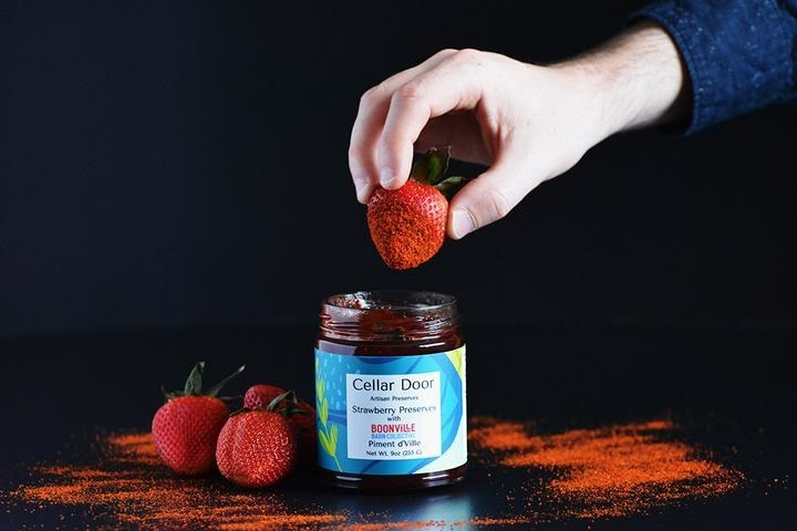 a hand dipping a strawberry into the jar of perserves