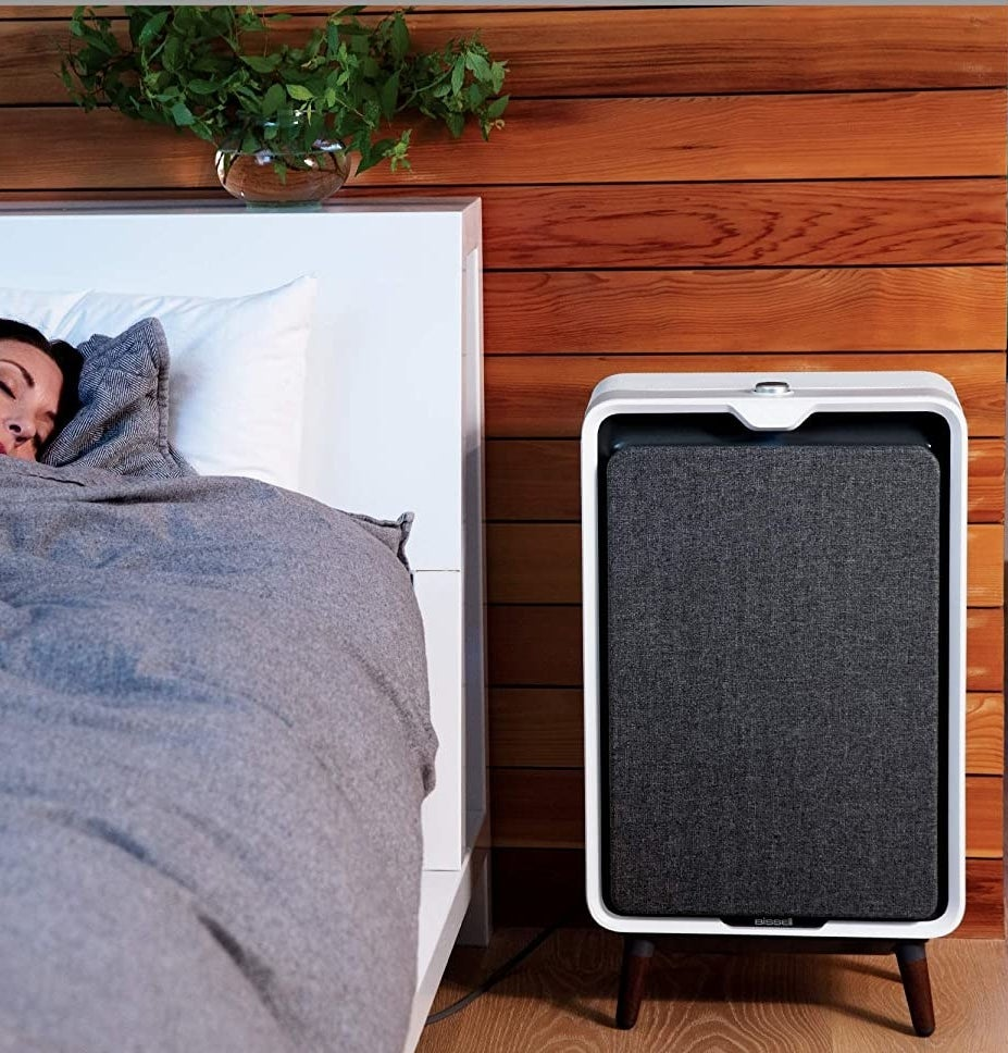 The air purifier next to a bed